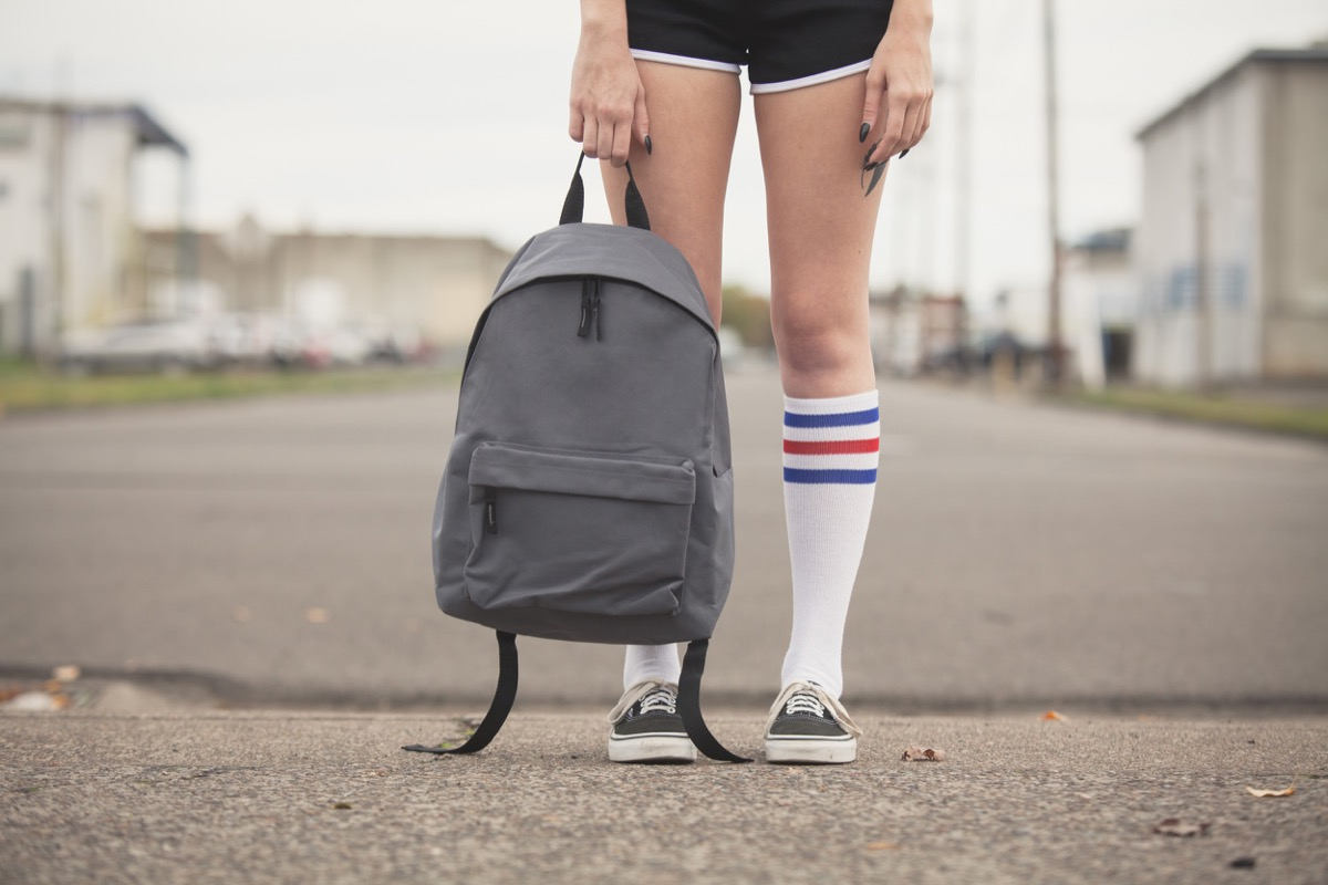 Girl holding generic backpack wearing black shorts and tube sock with tennis shoes standing on vacant street. - Image