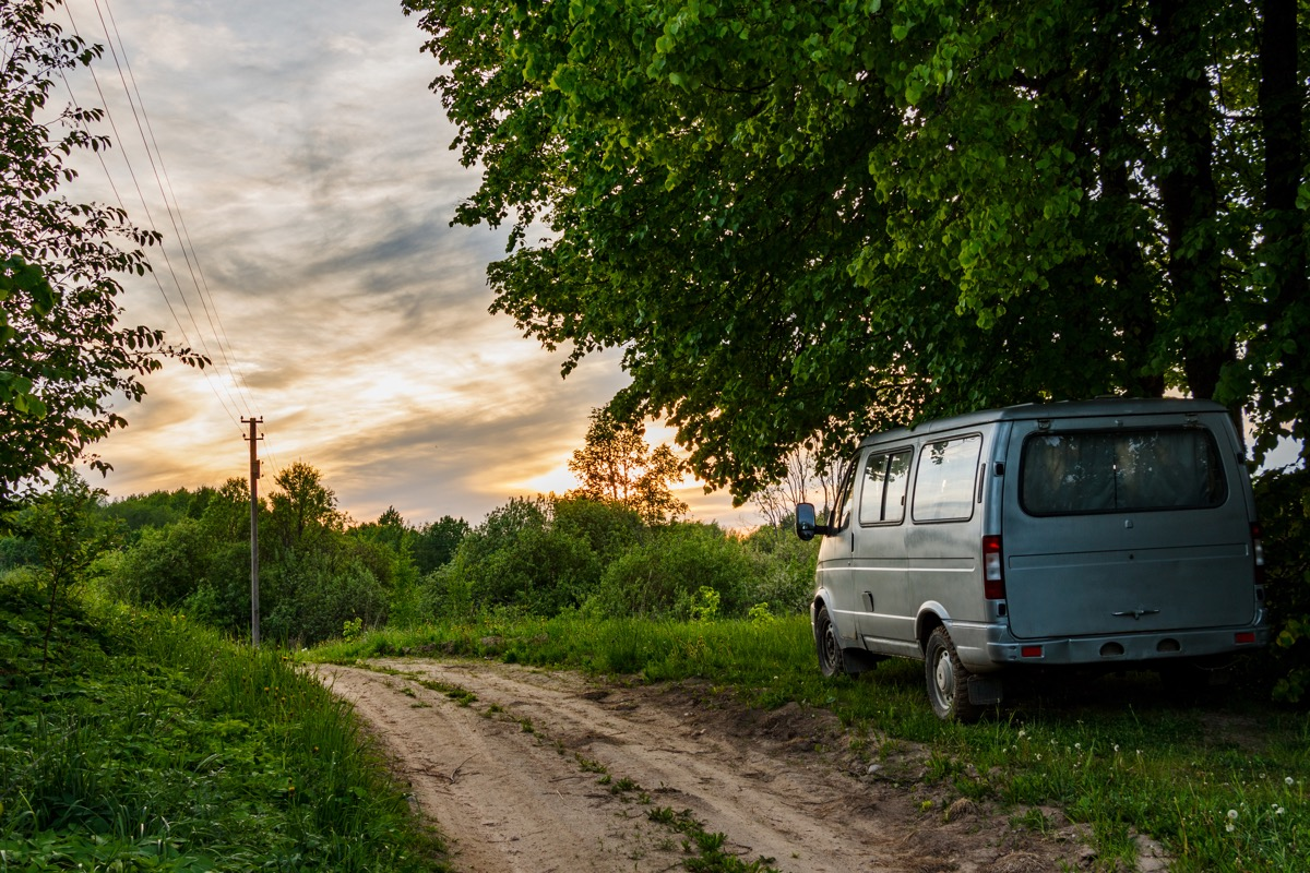 The minibus stands on the side of a dirt road. The machine stands under large linden trees. From behind you can see the sky and the sunset. - Image