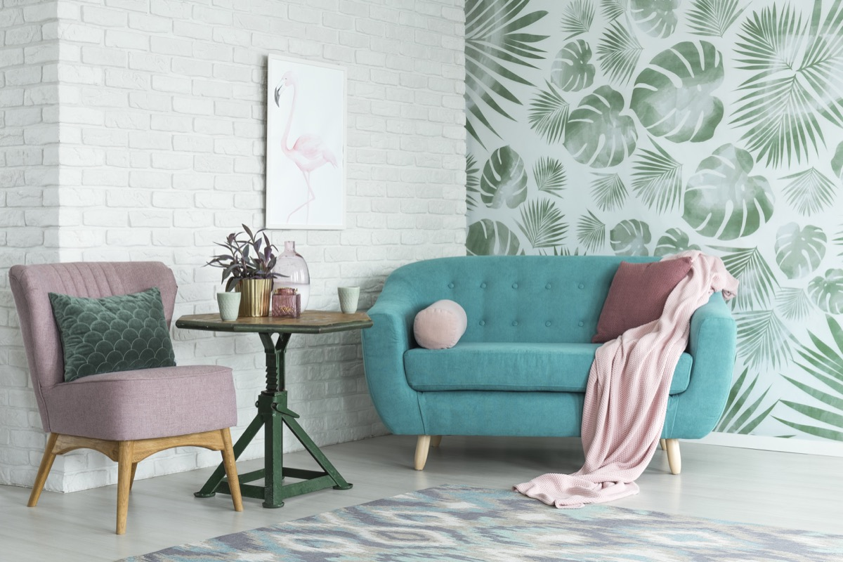 Living room with fern wallpaper and exposed brick