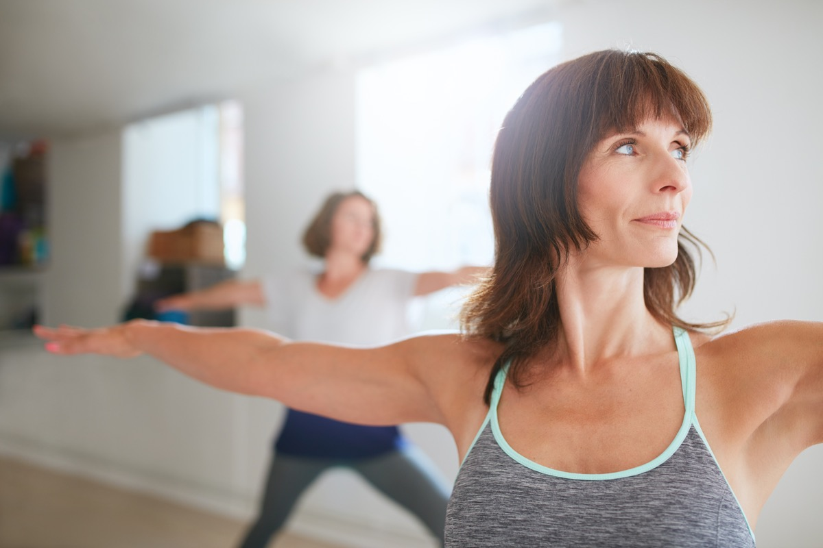 Woman doing warrior pose in yoga class