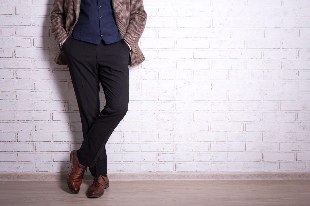 man wearing plaid blazer black pants and brown shoes