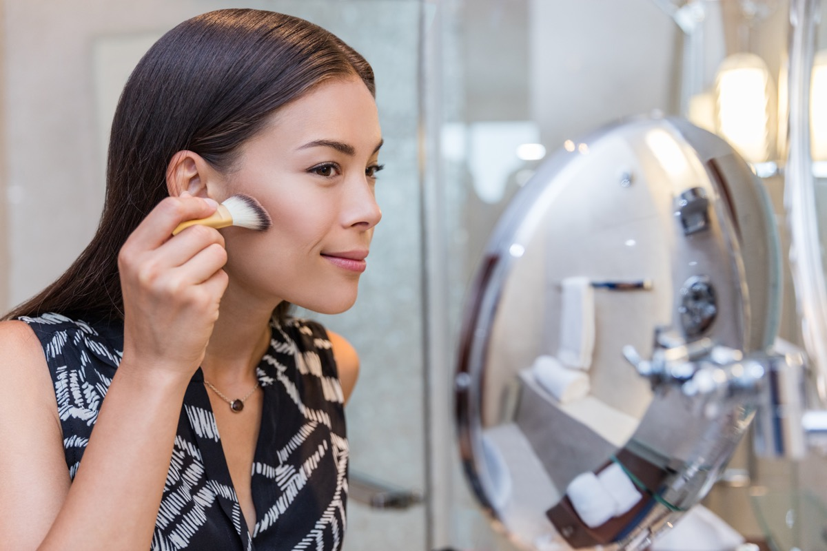 Woman applying bronzer makeup