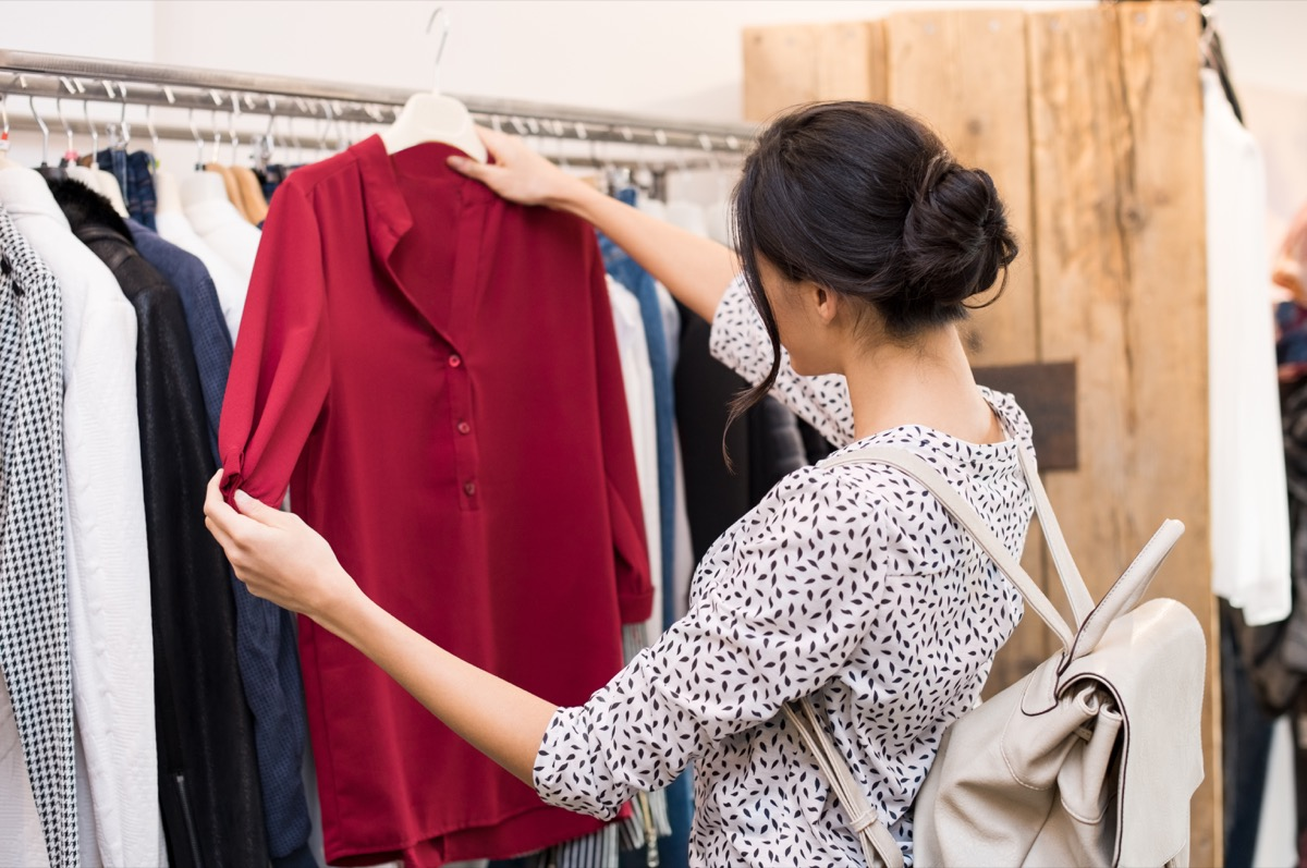 woman checking out a red top in a clothing store