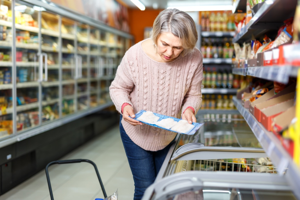Middle-aged woman buying frozen fish at the grocery store