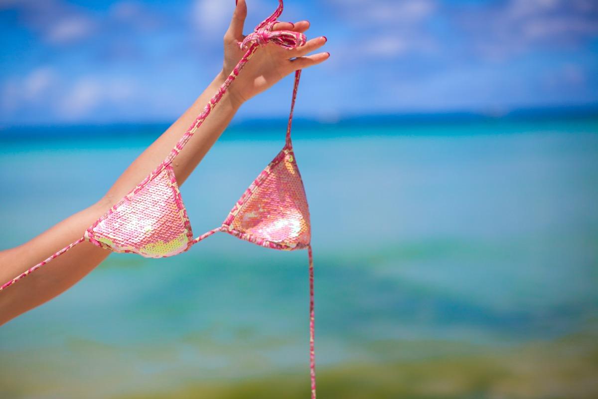 Woman holding tiny sequin bikini on the beach