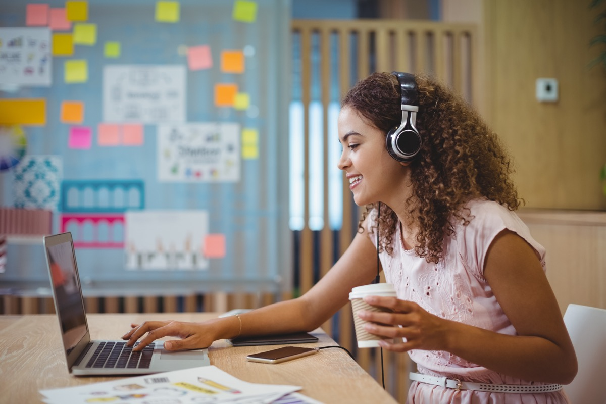 Female graphic designer listening song while using laptop in office