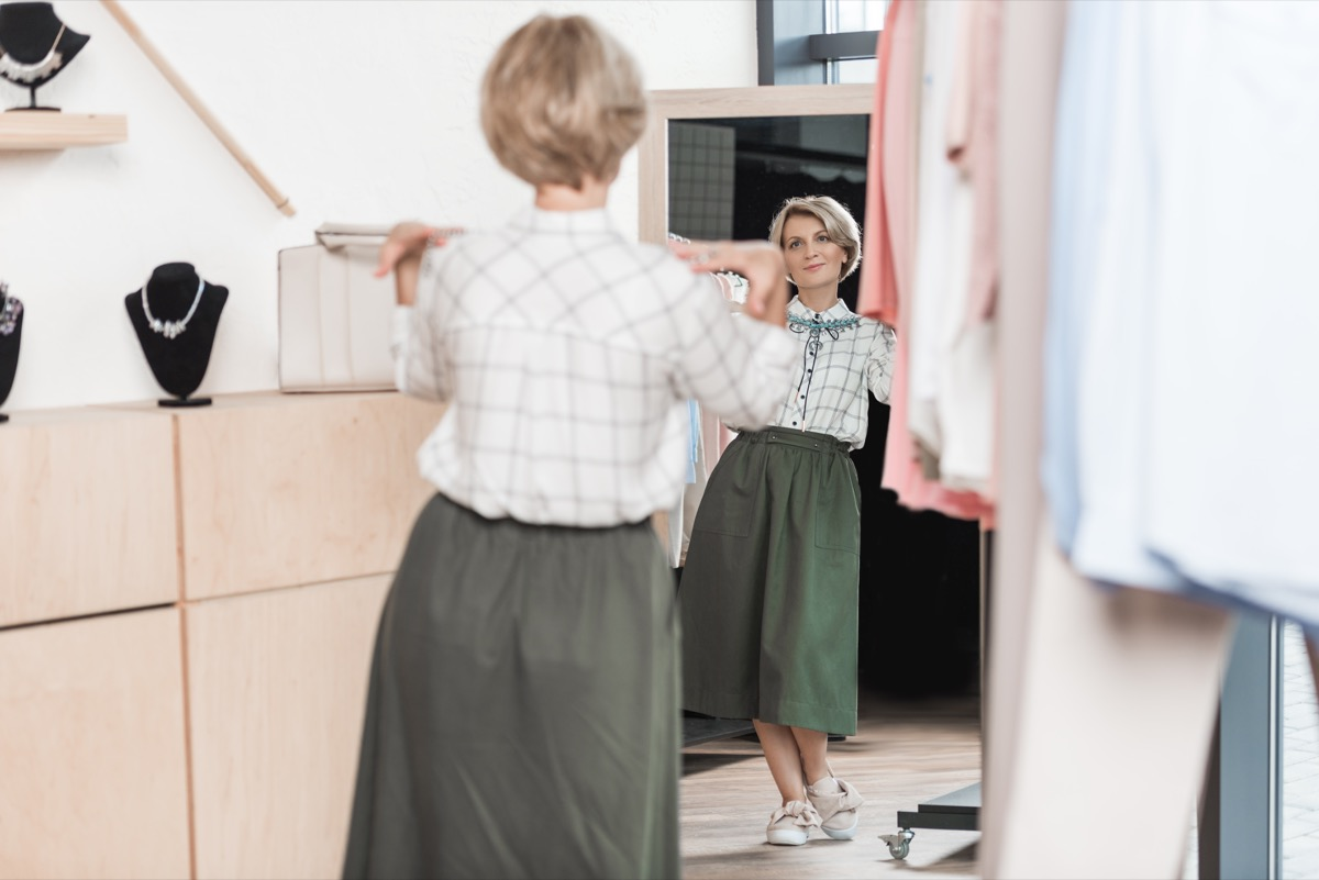 Woman looking at her outfit in the mirror