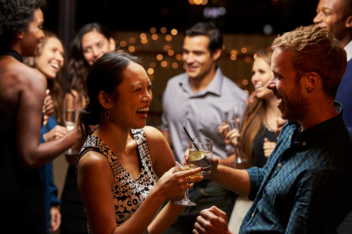 woman and man laughing in conversation at a cocktail party, bad jokes