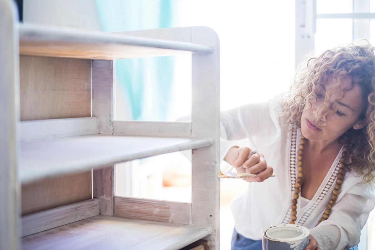 Woman painting a bookshelf white refurbishing furniture