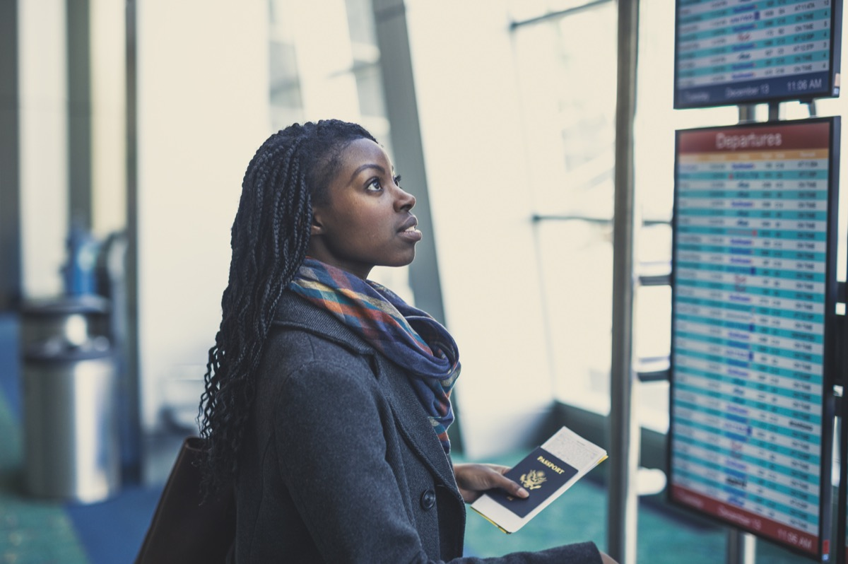 Young African American woman at airport holding passport and looking at the departures board