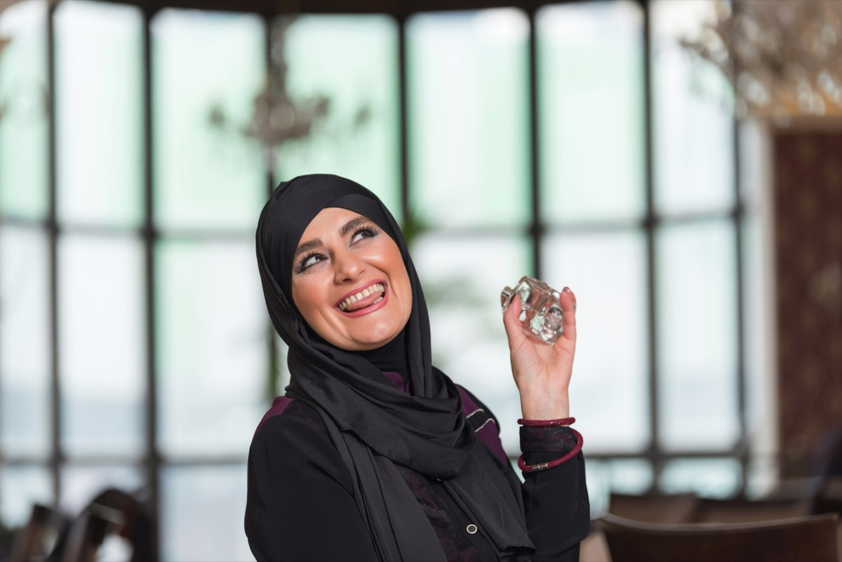 Muslim woman putting on perfume