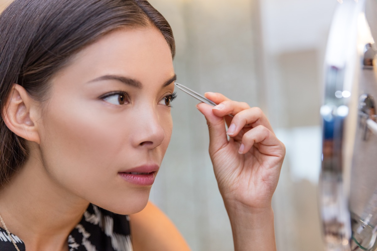 Asian woman plucking eyebrows with tweezers using eyebrow tweezer at home in bathroom makeup mirror. Closeup of a girl's face while she is removing her facial hairs. Eyebrows beauty car