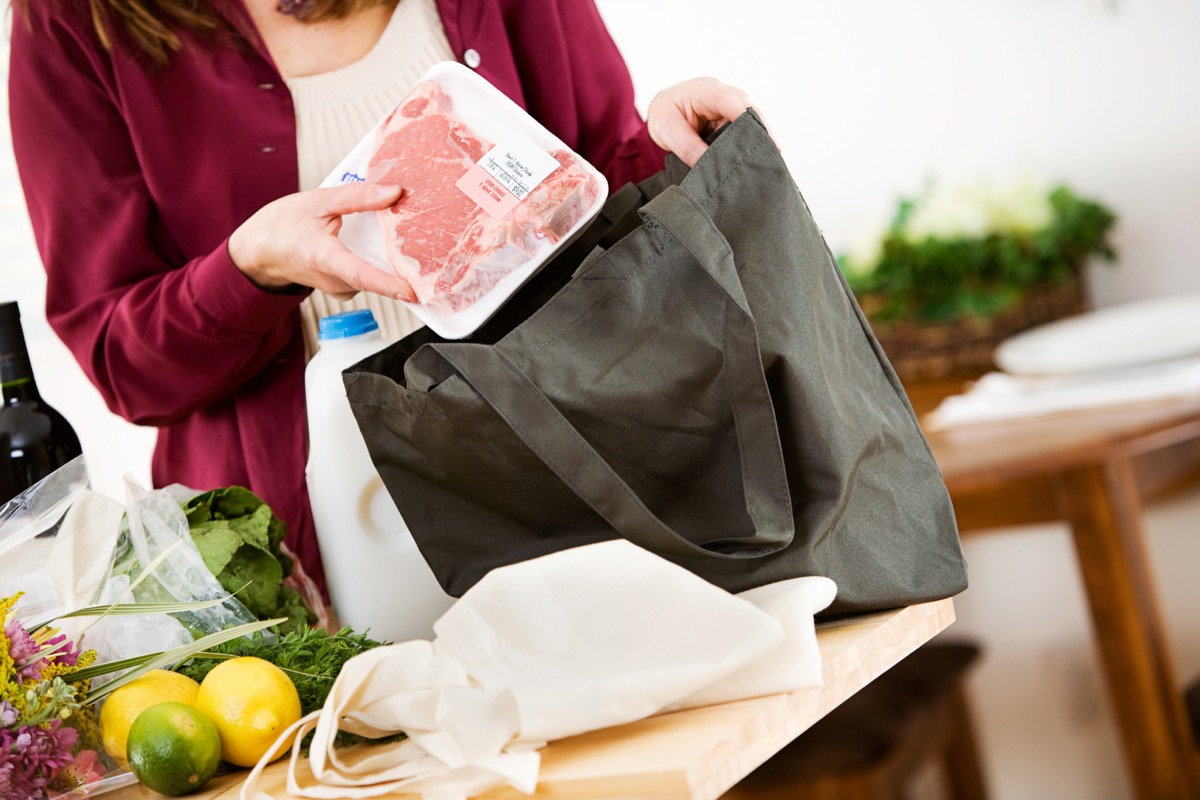 woman pulling meat out of a reusable shopping bag
