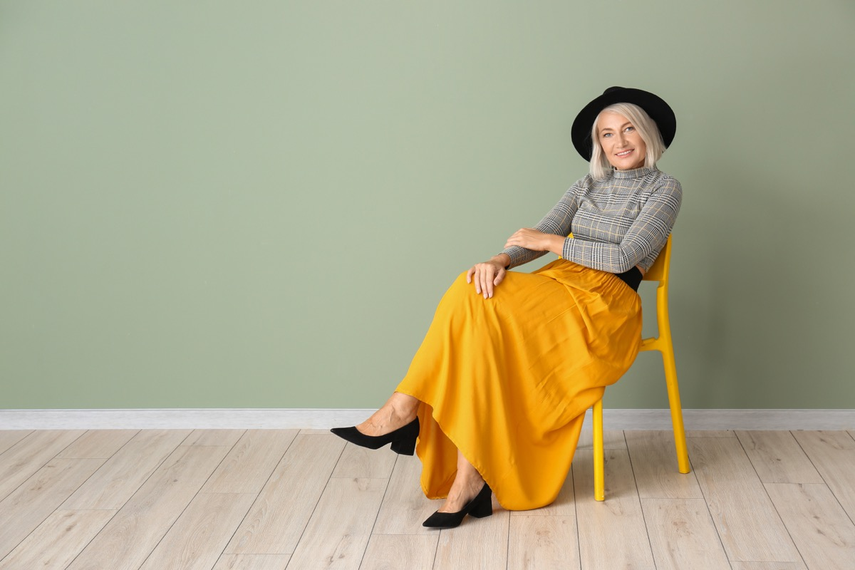Woman in 40s sitting in a chair wearing a bold bright yellow skirt outfit with a hat