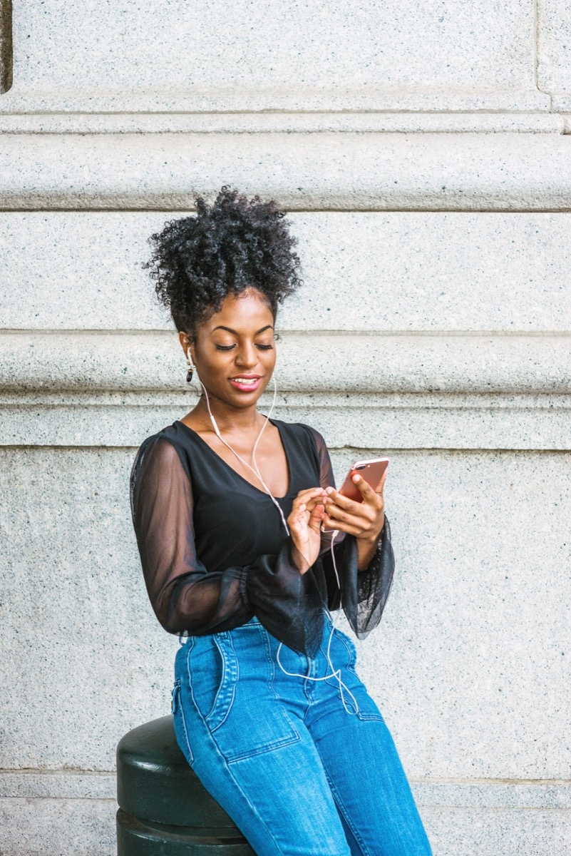 Woman texting and listening to music wearing a black shirt with sheer sleeves