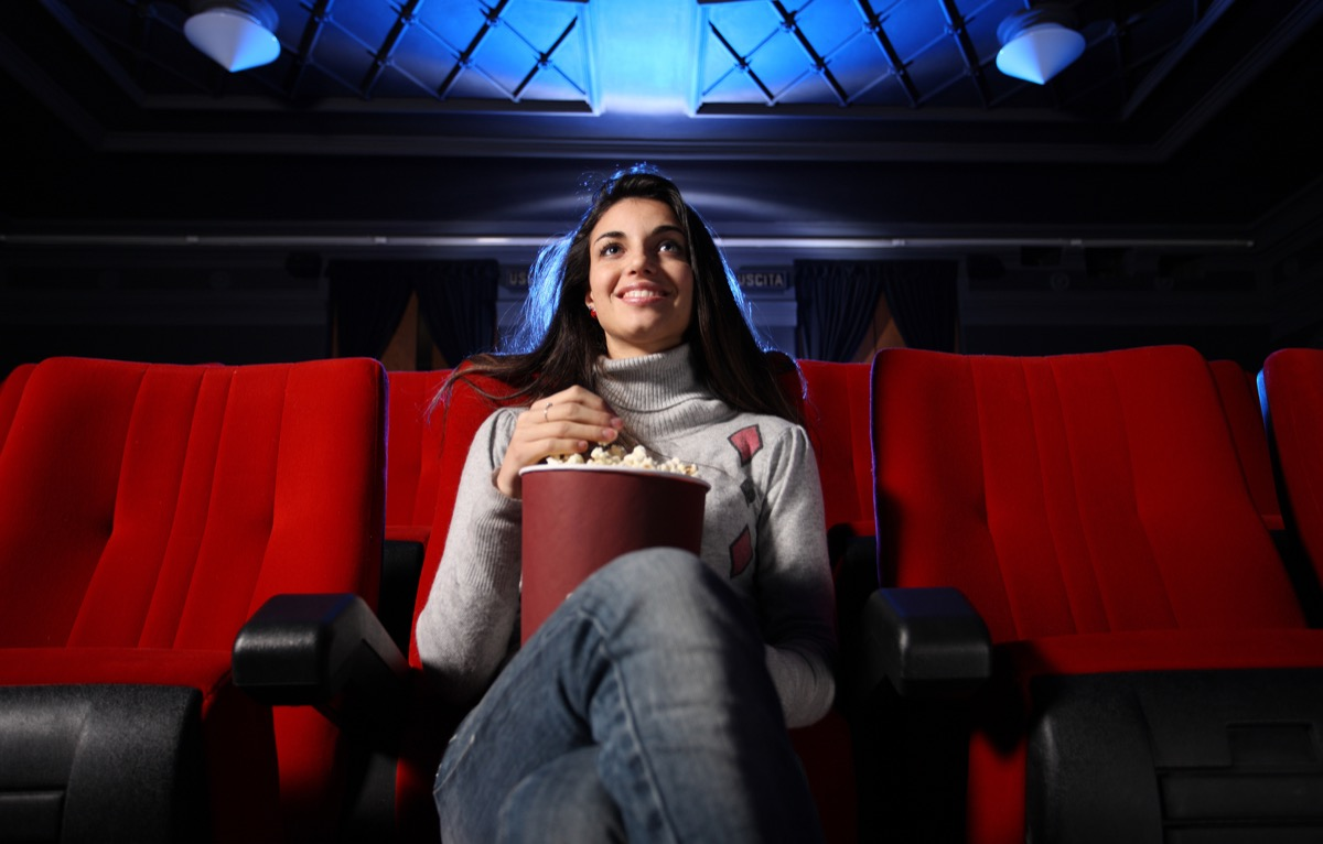 woman watching movie in movie theater alone self-care tips