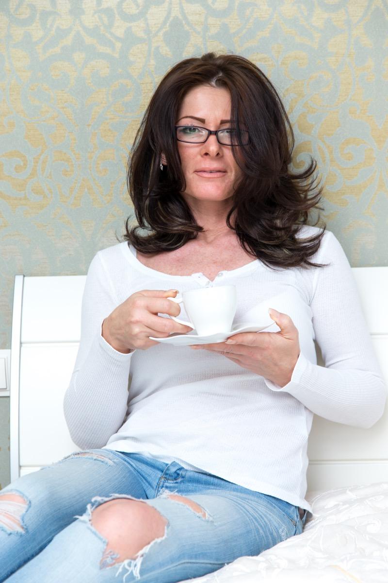 Woman wearing ripped jeans drinking tea 40s