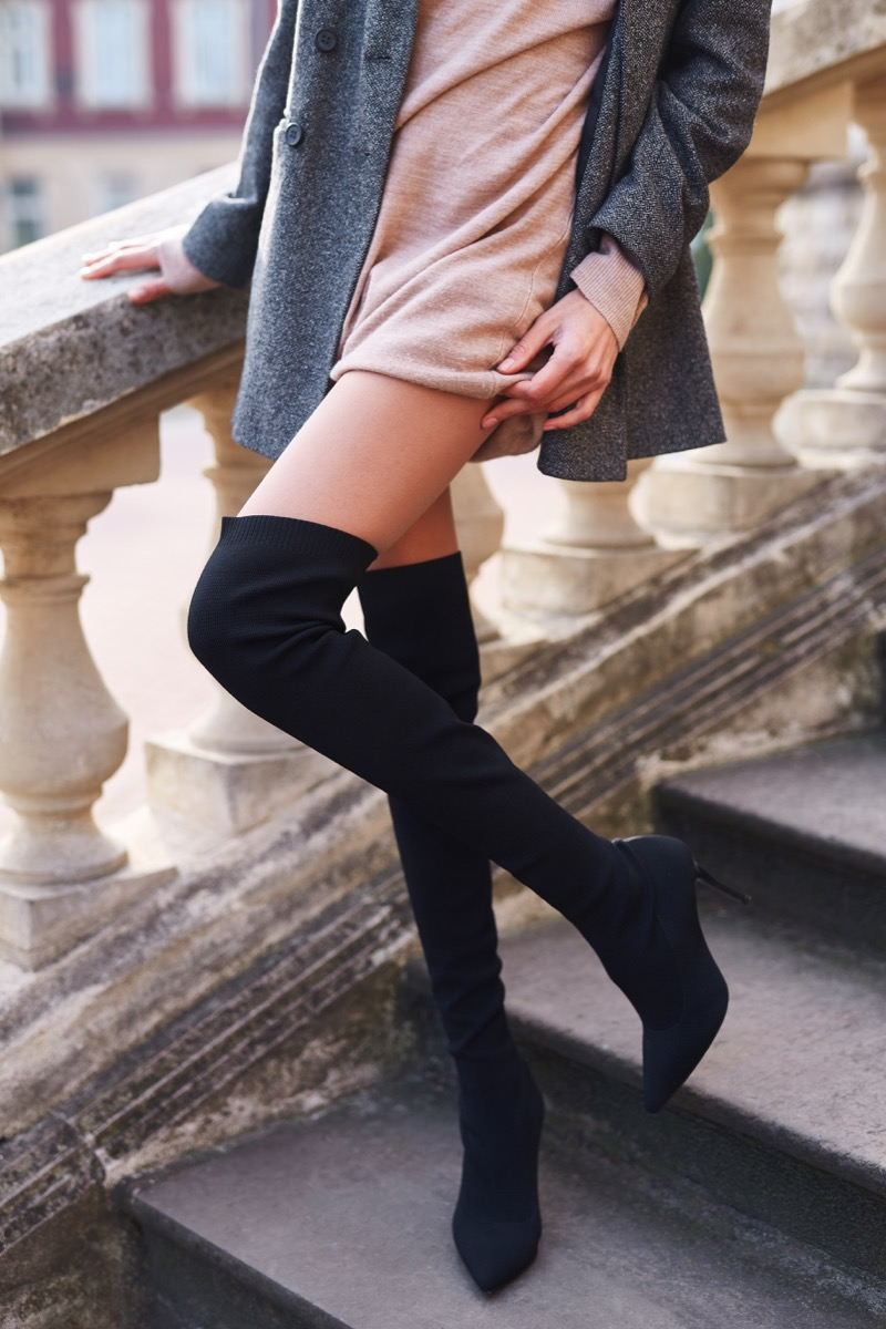 Woman wearing black over the knee high heeled boots