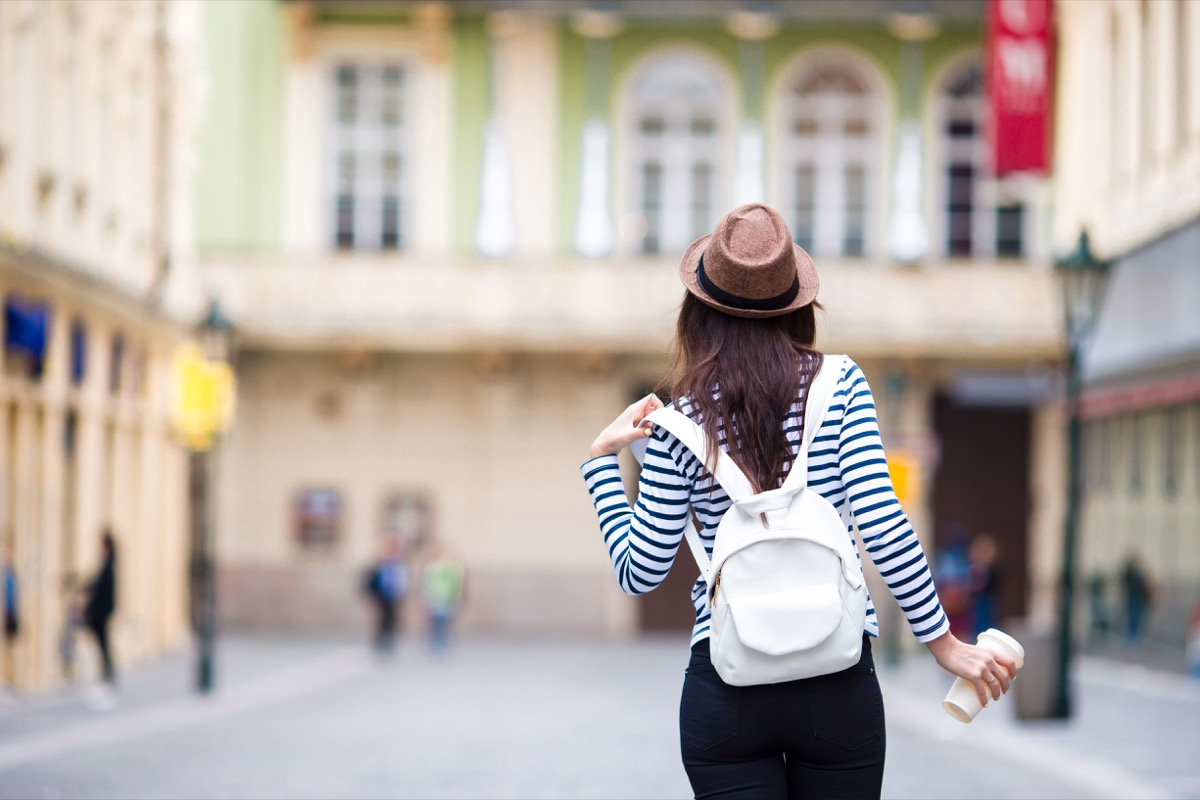 woman wearing a striped shirt and holding a white leather backpack