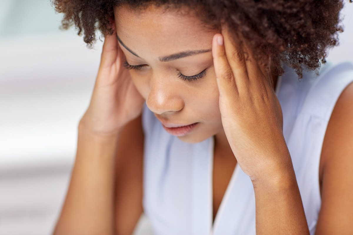 people, emotions, stress and health care concept - unhappy african american young woman touching her head and suffering from headache - Image