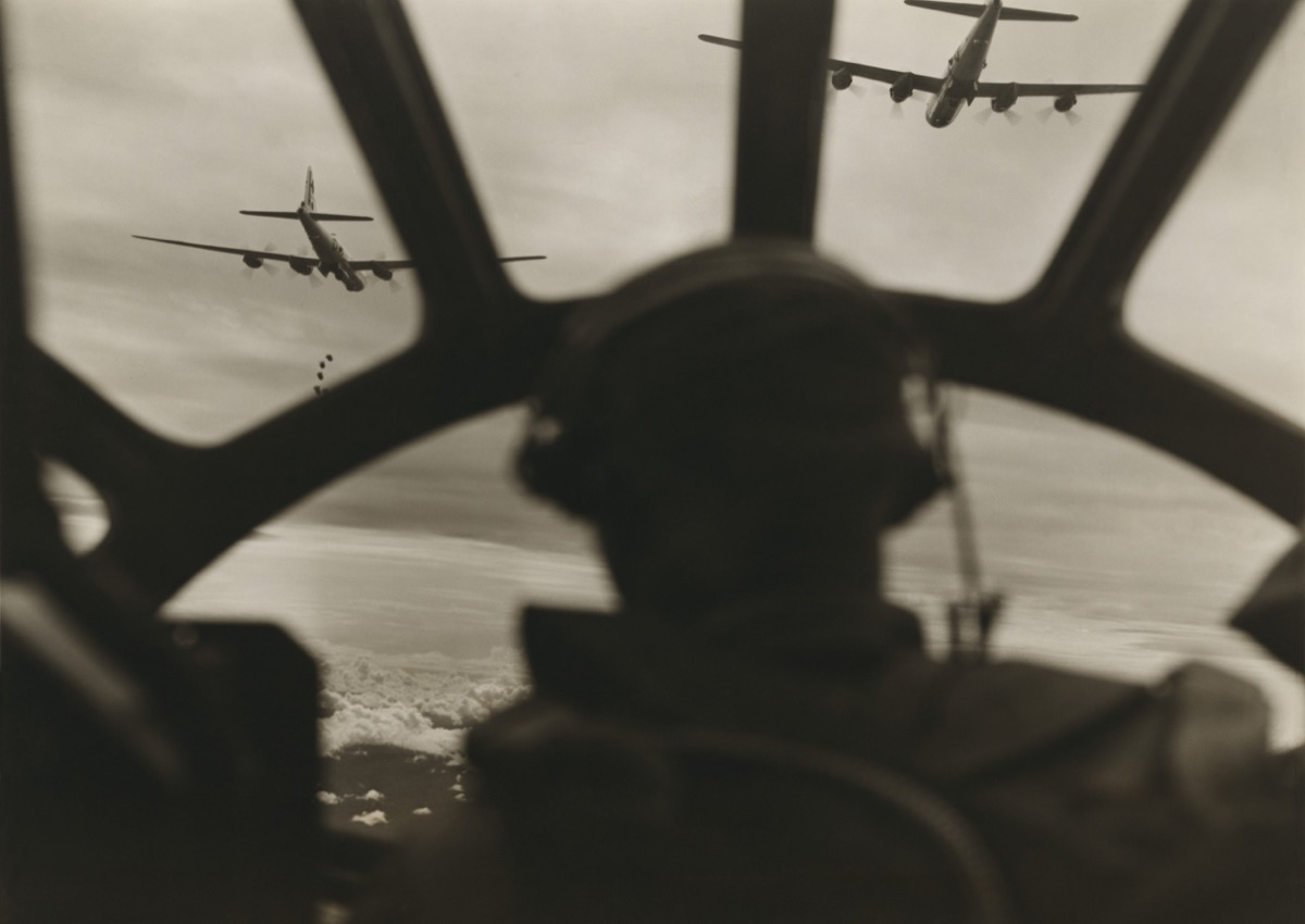Two B-29 Super-fortresses drop bombs over Malaya as seen from cockpit of third bomber during a run over the important railway yards and repair shops utilized by the Japanese at Kuala Lumpur
