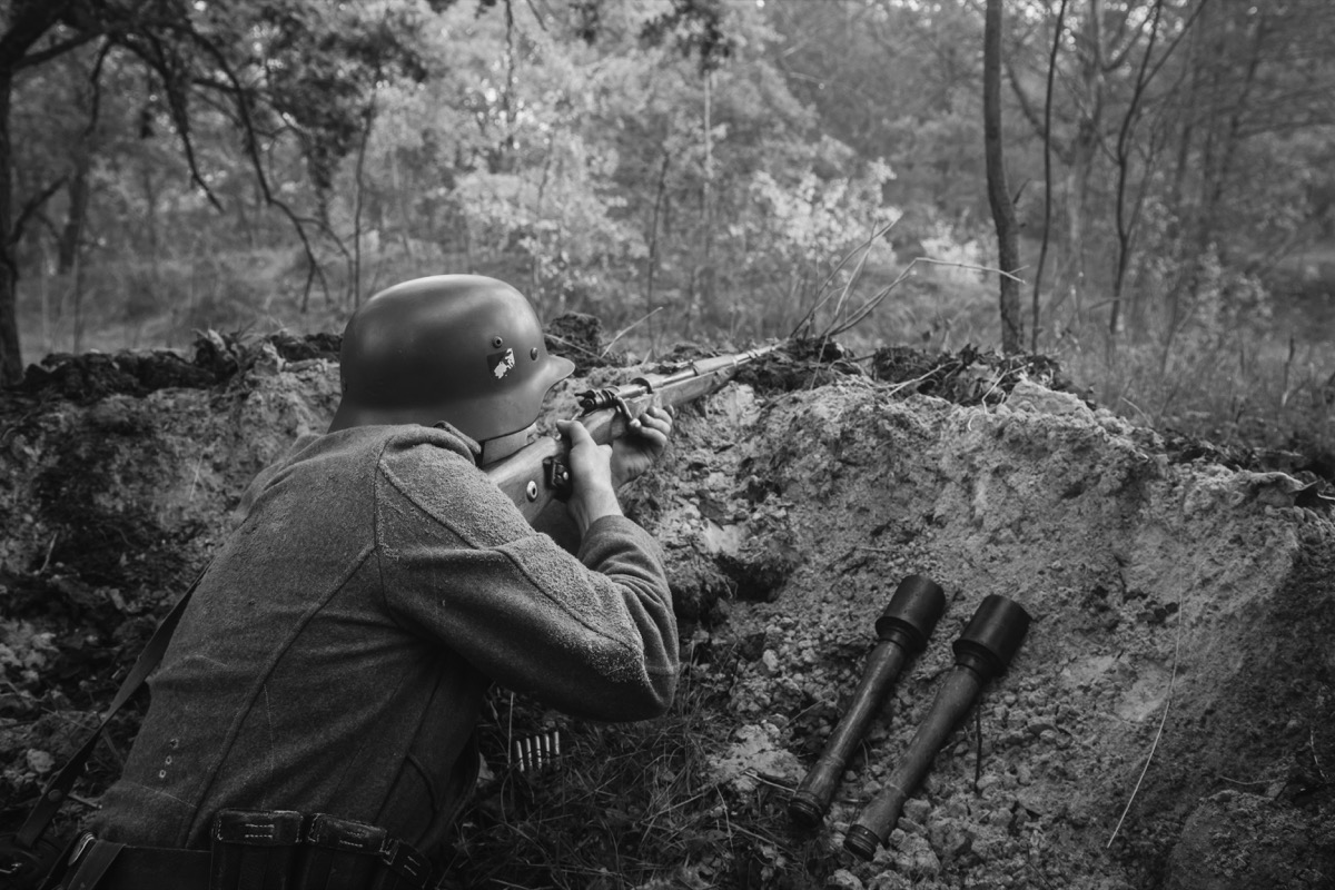 Unidentified Re-enactor Dressed As German Wehrmacht Infantry Soldier In World War II Hidden Sitting With Rifle Weapon In An Ambush In Trench In Autumn Forest. Photo In Black And White Colors.