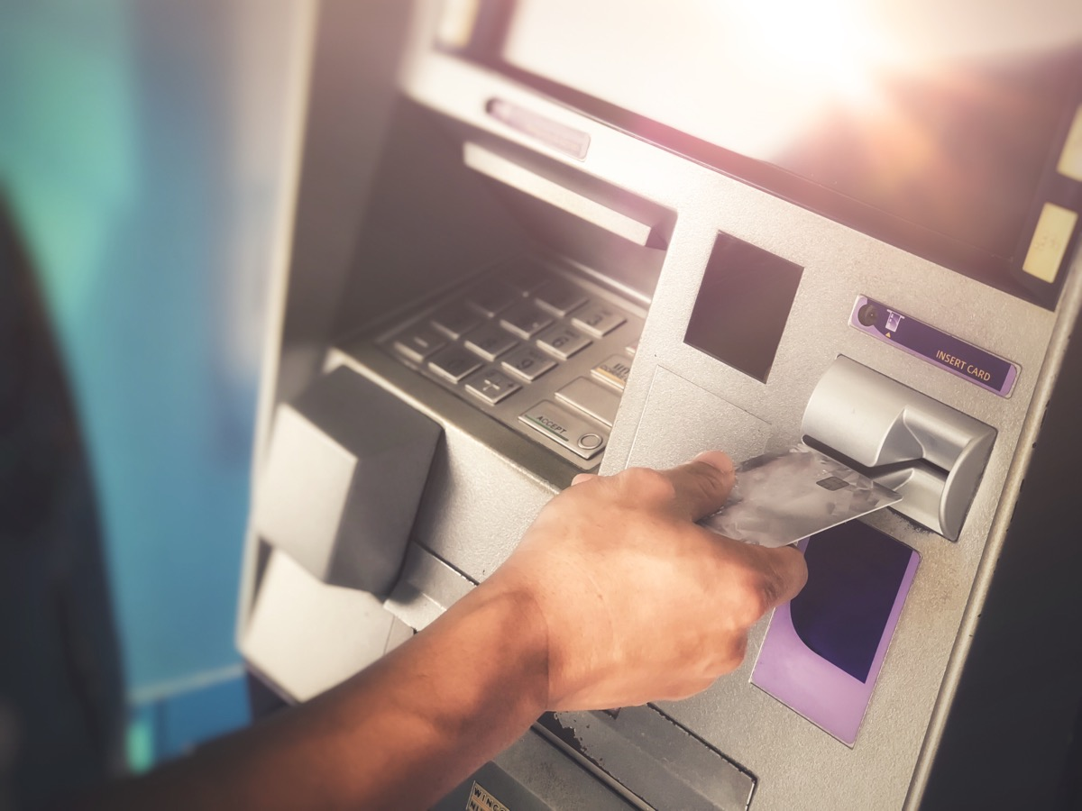 Man's hand inserting ATM credit card into bank machine to transfer money or withdraw - Image