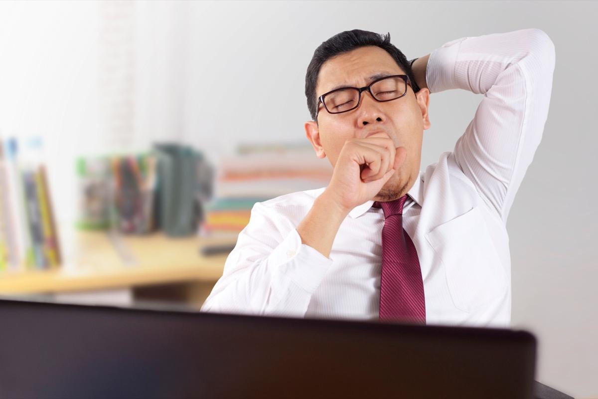 Asian Man Sitting at His Desk at Work Yawning {Allergy Symptoms}