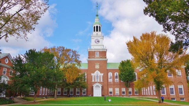 Looking down the Dartmouth Green with trees beginning to show fall colors and a blue sky with puffy white clouds on a nice autumn day the Baker Library and its bell tower is in the background. - Image
