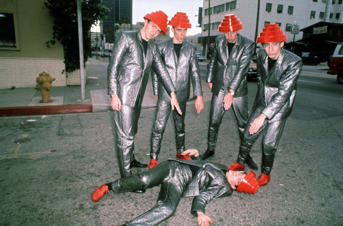 devo wearing silver suits and their signature red hats