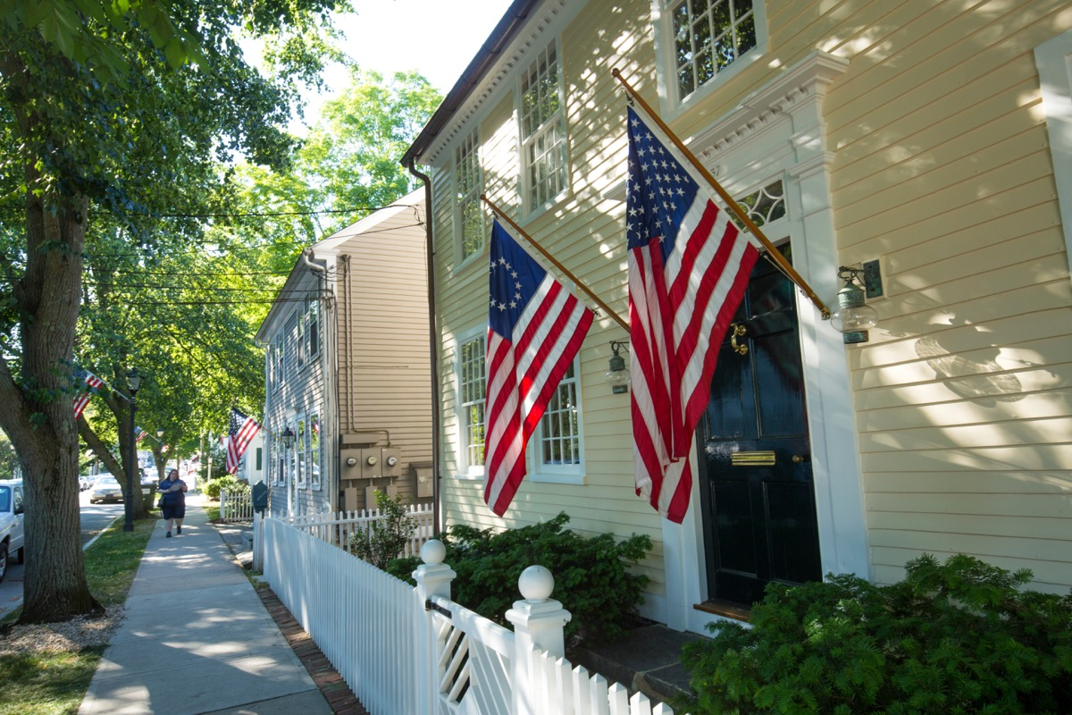 ESSEX, CONNECTICUT, USA - June 19, 2018: American flags and a white picket fence line Main Street in Essex, an all-American village. - Image