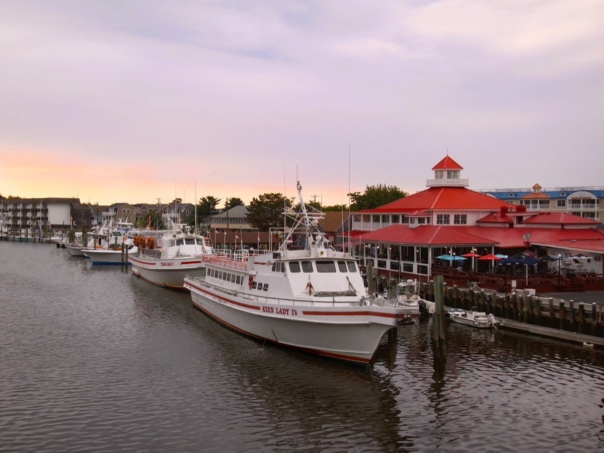 LEWES, DELAWARE - AUGUST 29, 2017: Tour boats and fishing boats are moored in the harbor at sunset in Lewes, Delaware, a United States eastern shore town rich in Civil War history. - Image