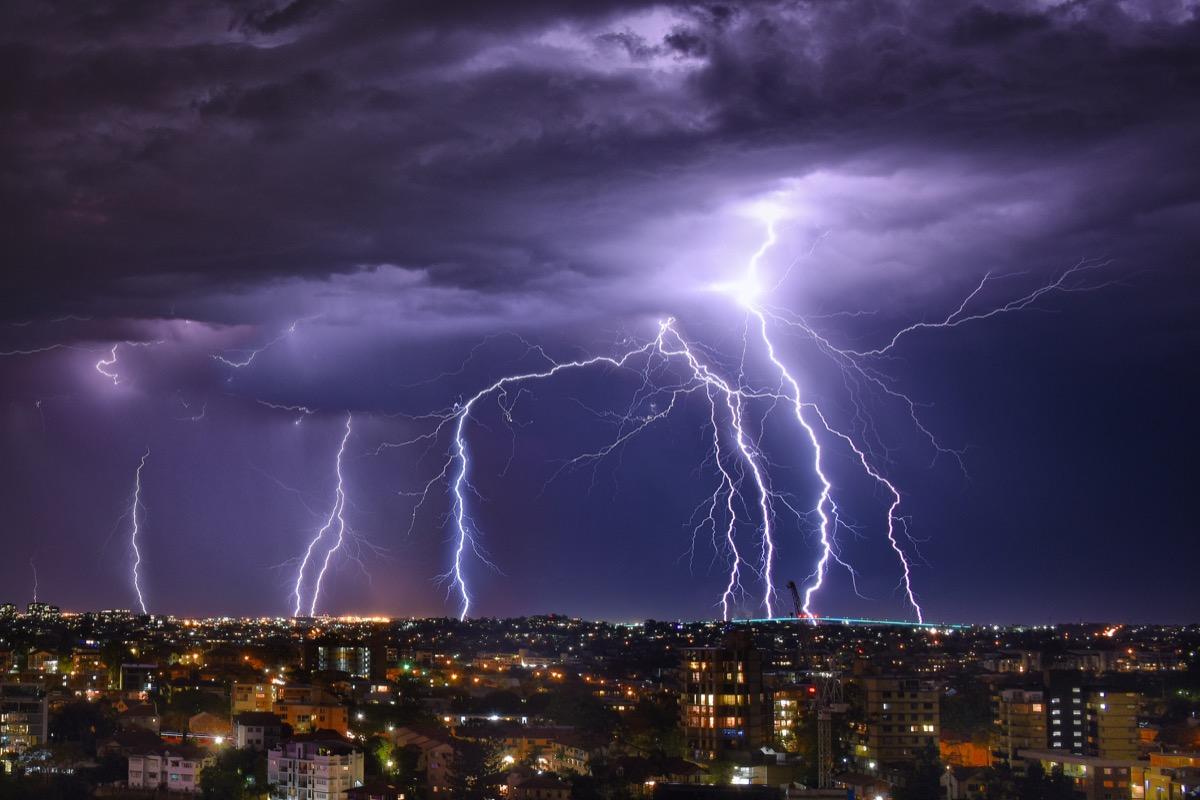 Lightning storm at night amid purple sky in Brisbane City