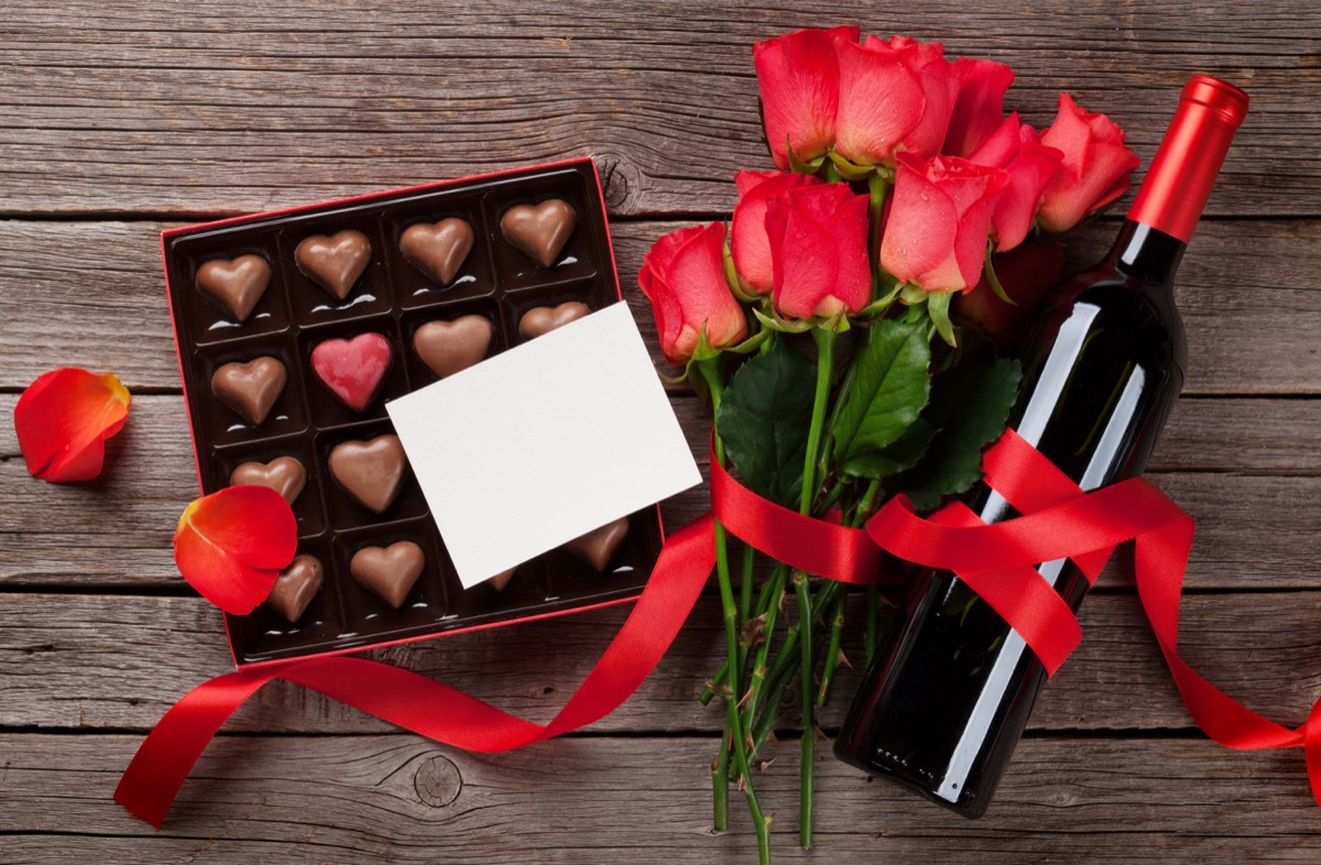 Valentines day with red roses, wine bottle and chocolate box on wooden table. Top view with space for your text - Image