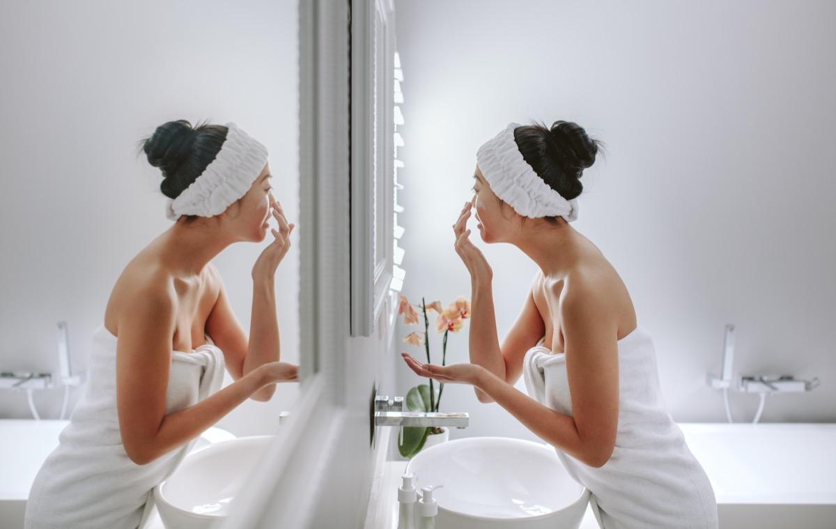 Woman applying cream in bathroom