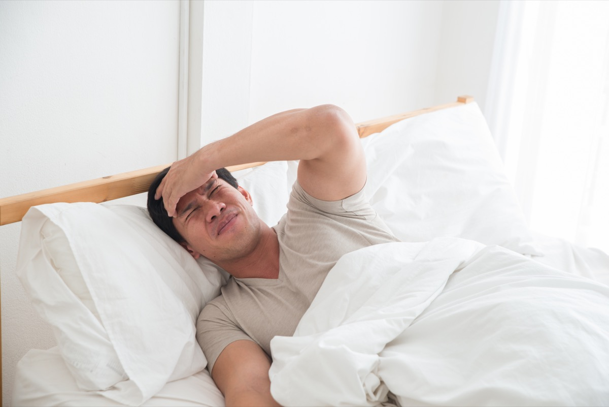 Asian man in bed with a headache