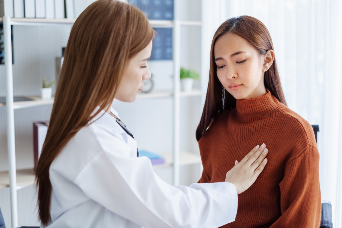Asian woman getting her breasts examined at the doctor's office