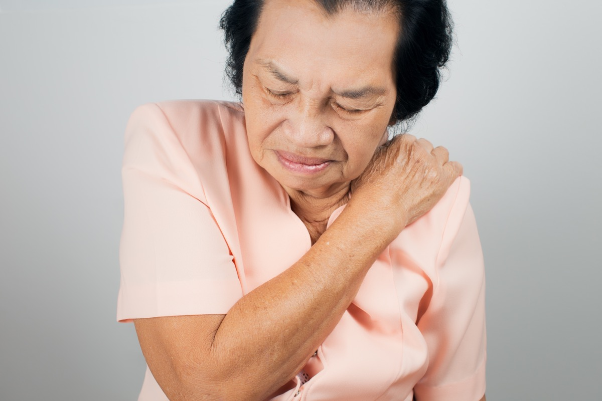 Asian woman suffering from shoulder pain