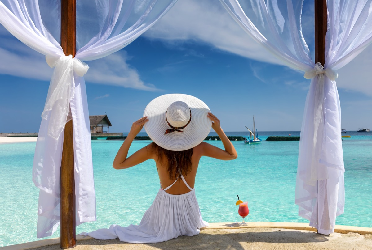 Beautiful woman with white hat enjoys her summer holiday in the tropics things burglars know