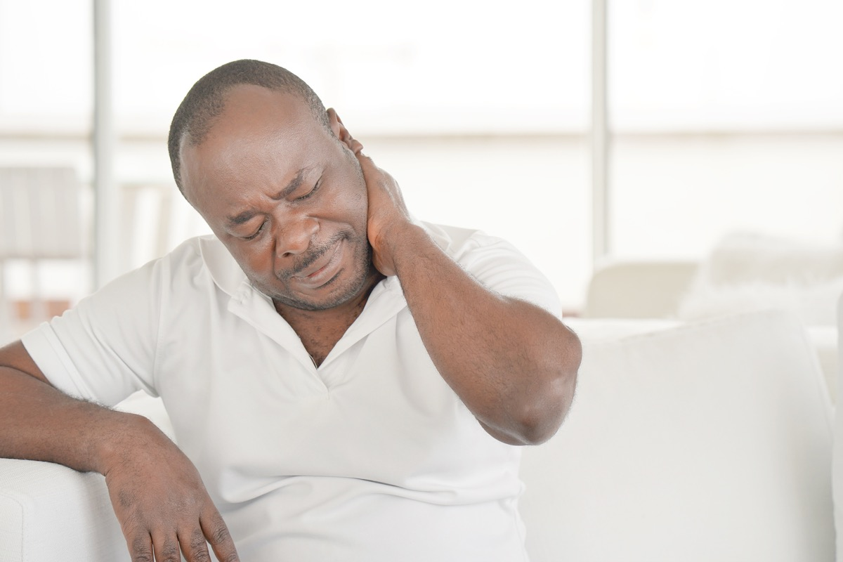 Senior man suffering from neck pain at home on couch.