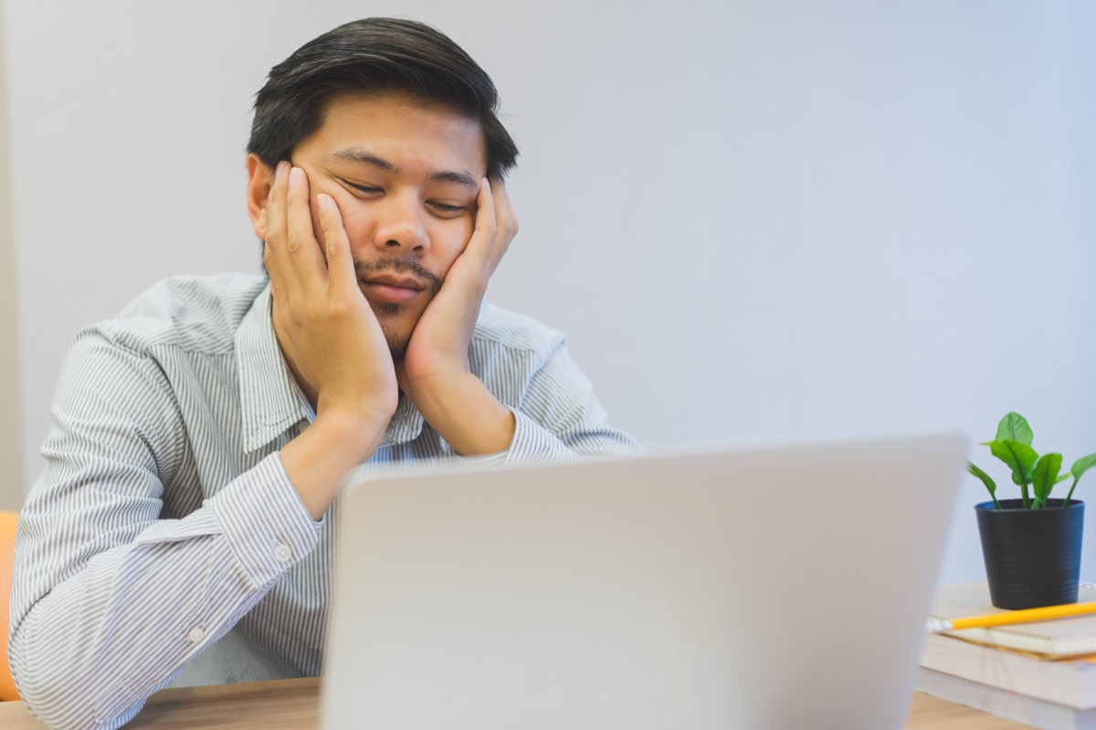 Man is Sitting by His Computer Bored at Work Signs of Burnout