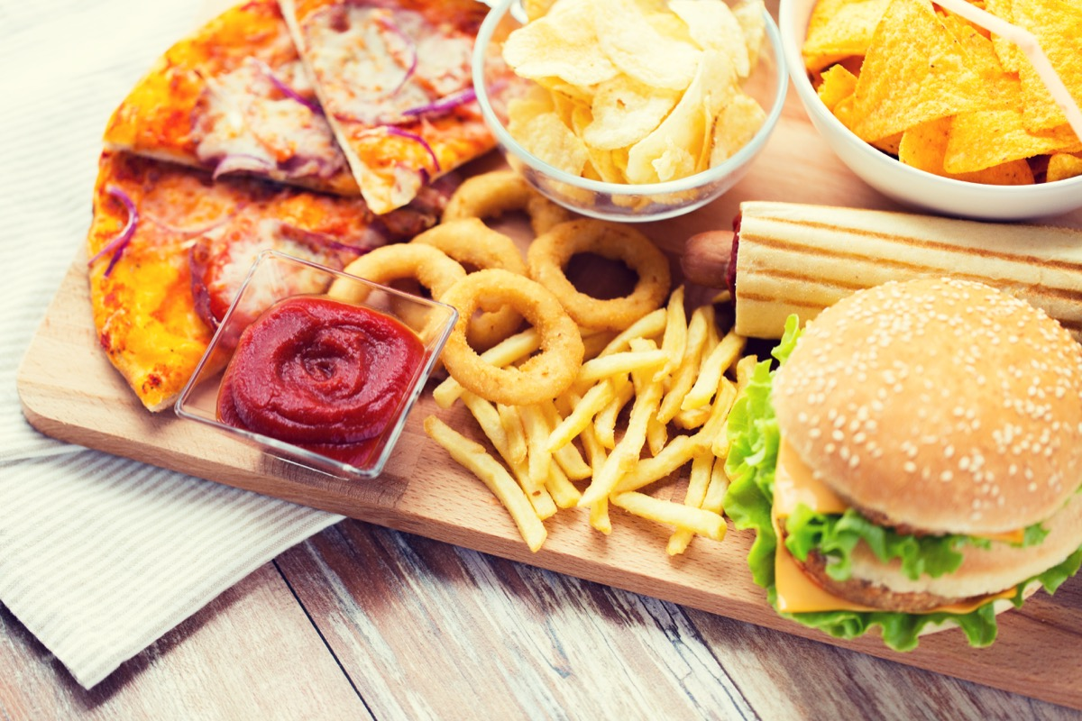 fast food and unhealthy eating concept - close up of hamburger or cheeseburger, deep-fried squid rings, french fries, pizza and ketchup on wooden table top view - Image