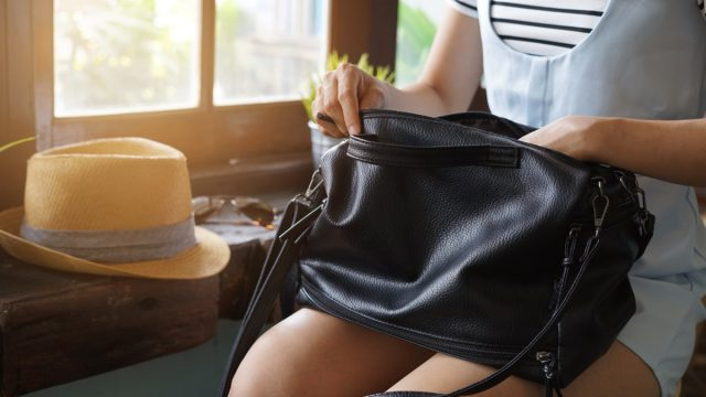 Young woman looking for something in her purse - Image