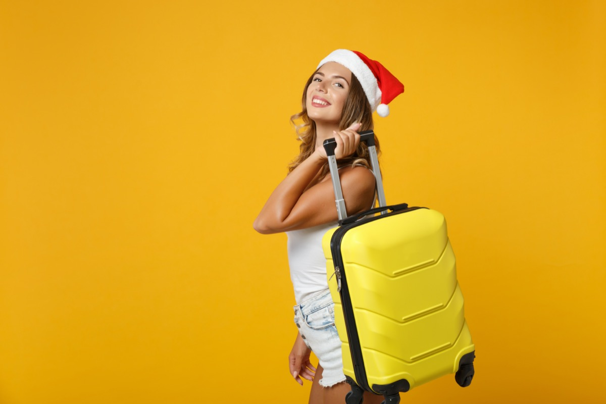 girl wearing santa hat holding her luggage by the shoulder