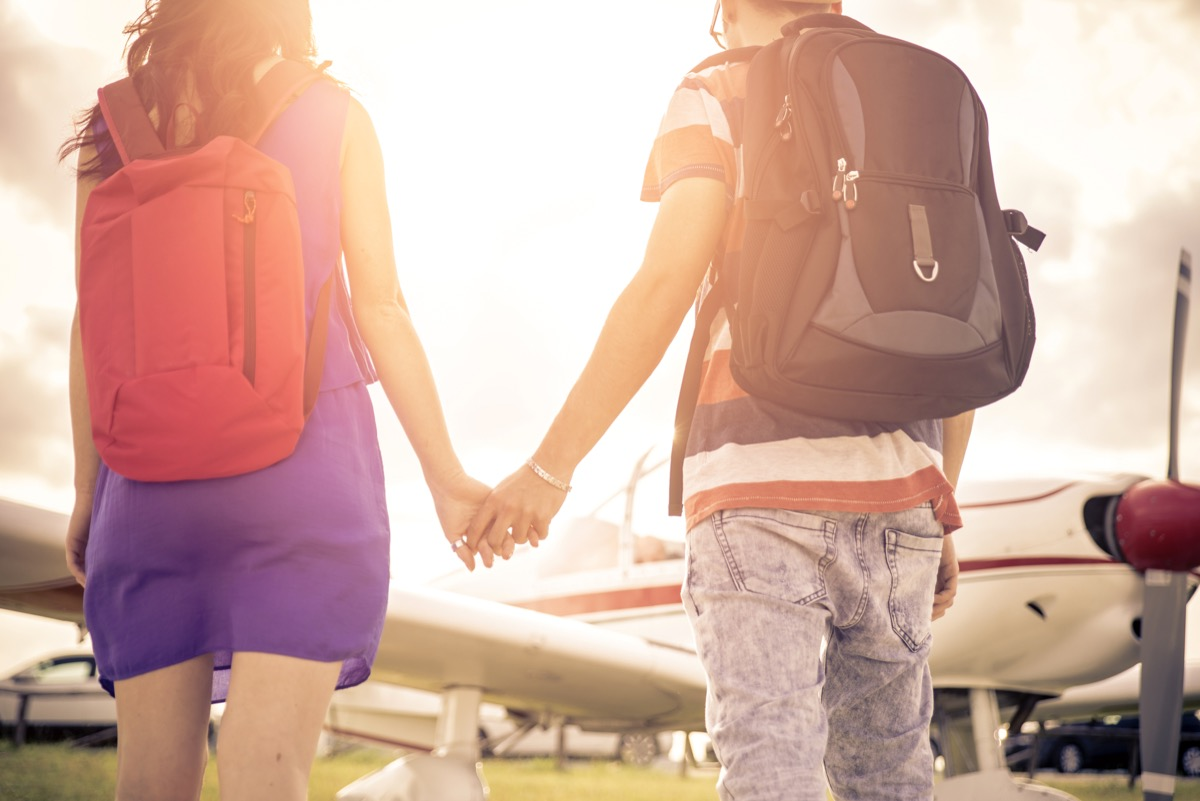 Couple getting on airplane booking cheap flights