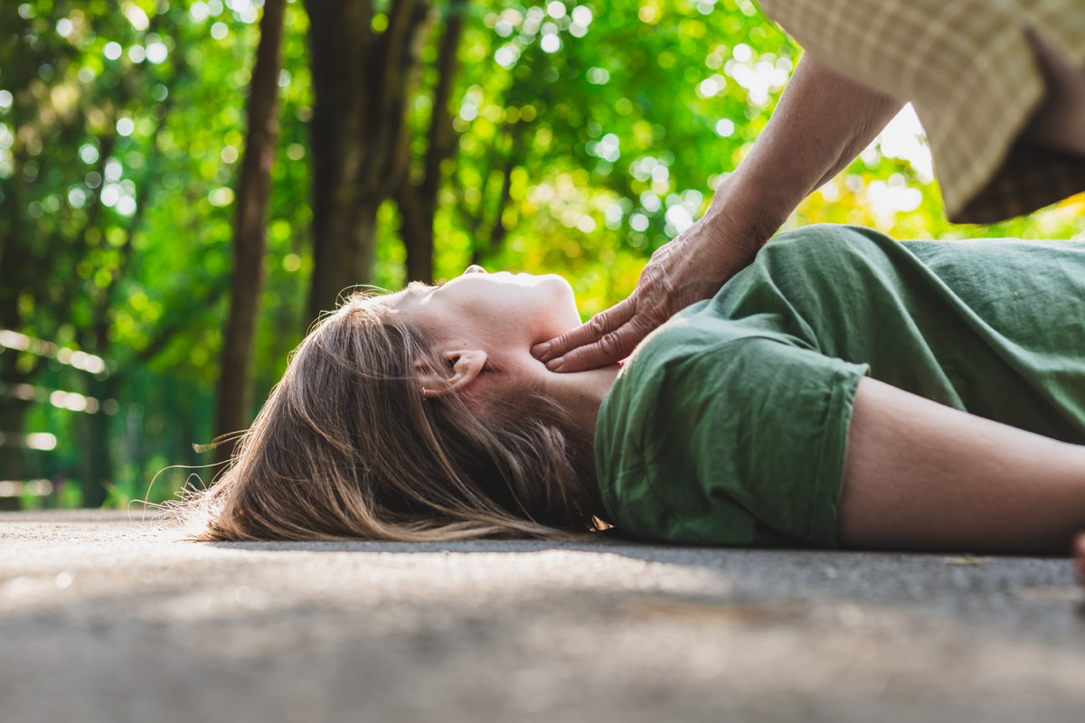 unconscious fainted girl having pulse checked by an old woman - Teenager lying on the ground while her pulse is verified by an elder citizen on teen's carotid artery (Unconscious fainted girl having pulse checked by an old woman - Teenager lying