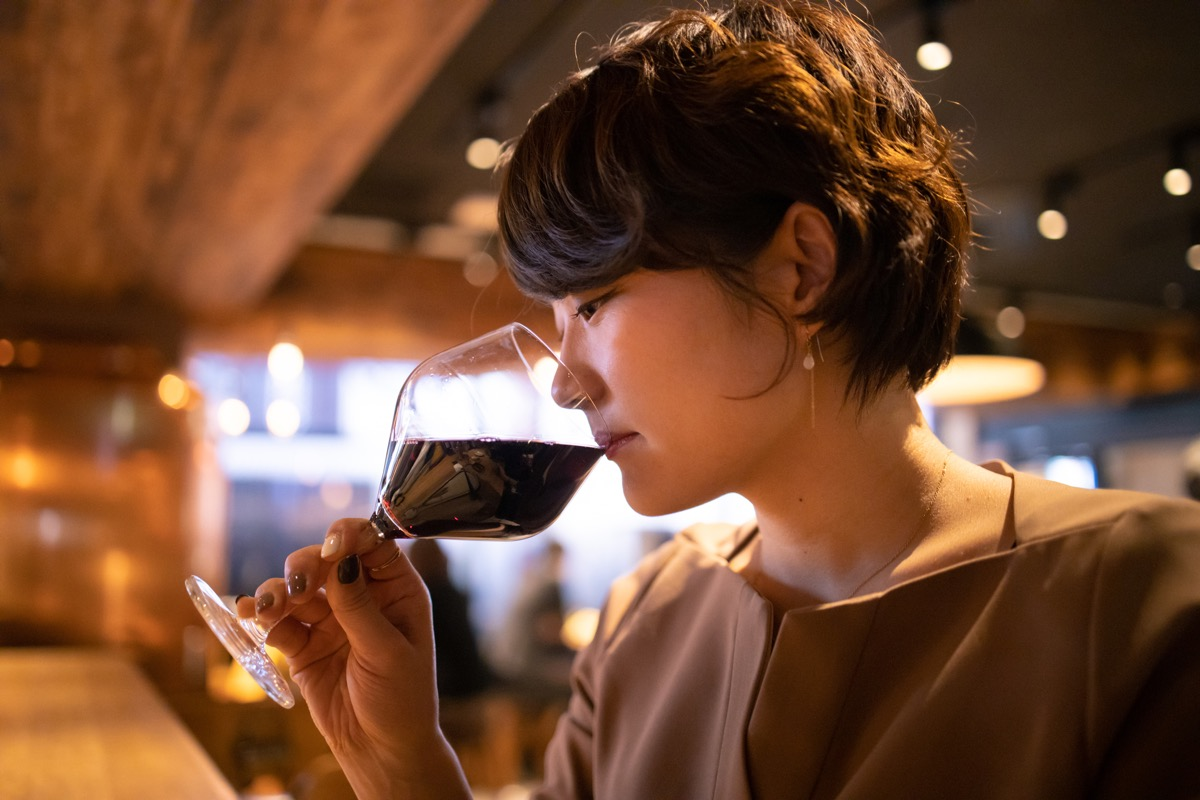 Young woman drinking red wine at bar