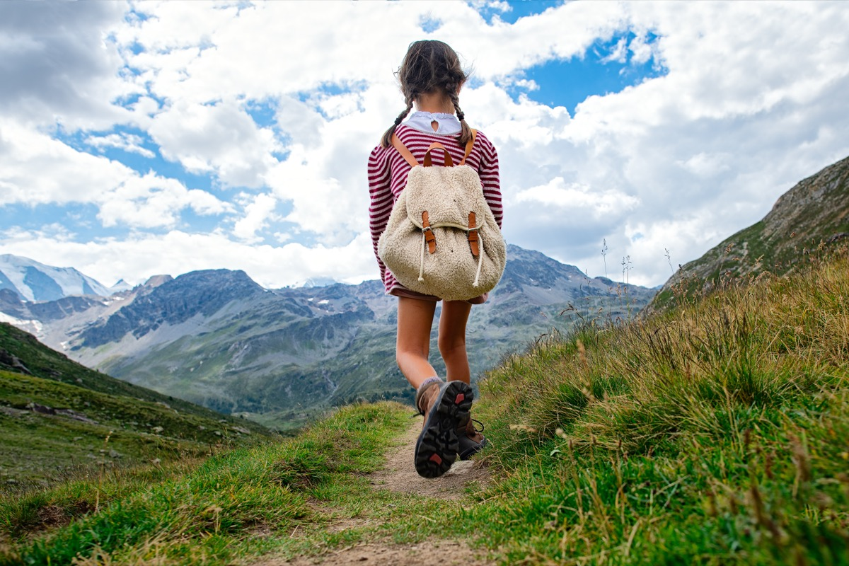 Little girl walks on mountain trail during an excursion. with the backpack. - Image