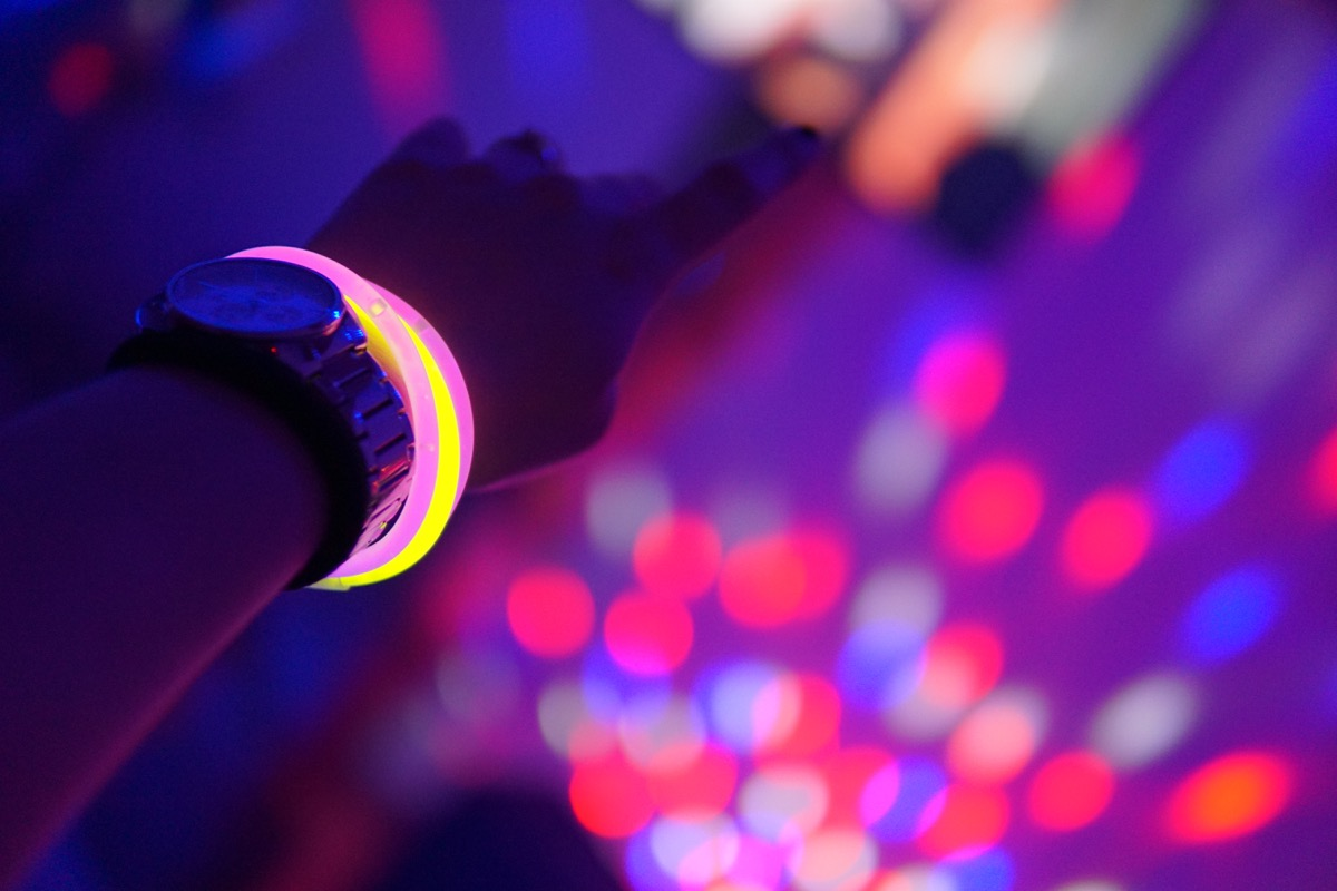 Hand with a watch and pink and yellow neon bracelets in the air during a neon party with blurry lights in the background - Image