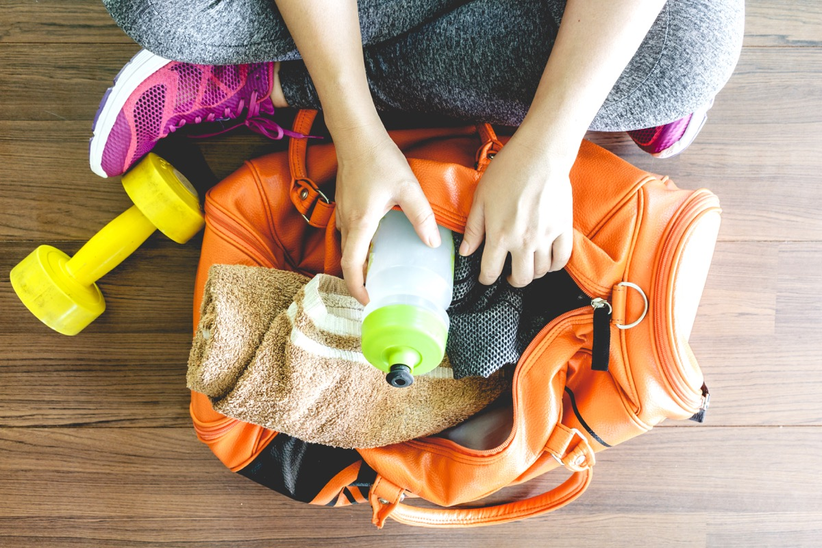 woman going through gym bag full of dirty clothes